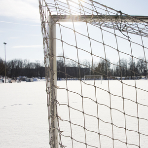 Snowbound football pitch seen from the back of the net